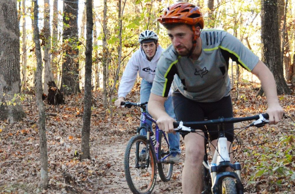 Cyclists ride on Cane Creek Park&#39s mountain bike trail.