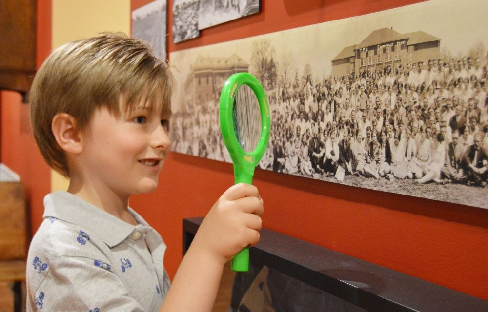 A boy looks through a magnifying glass at the Cookeville History Museum.