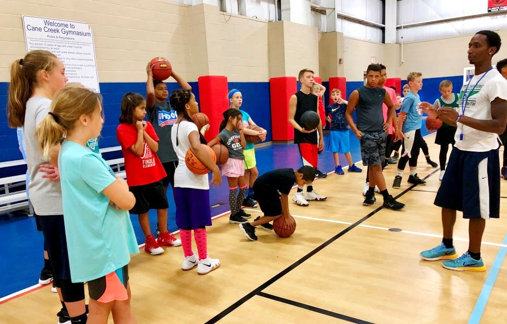 Kids gather during basketball camp at Cane Creek Gymnasium.
