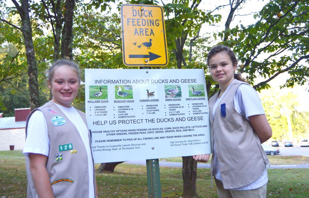 Girl Scouts show their duck feeding sign at Cane Creek Park.