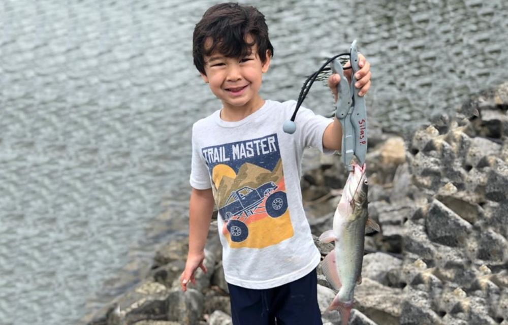 A boy shows a fish he caught at Cane Creek Park.