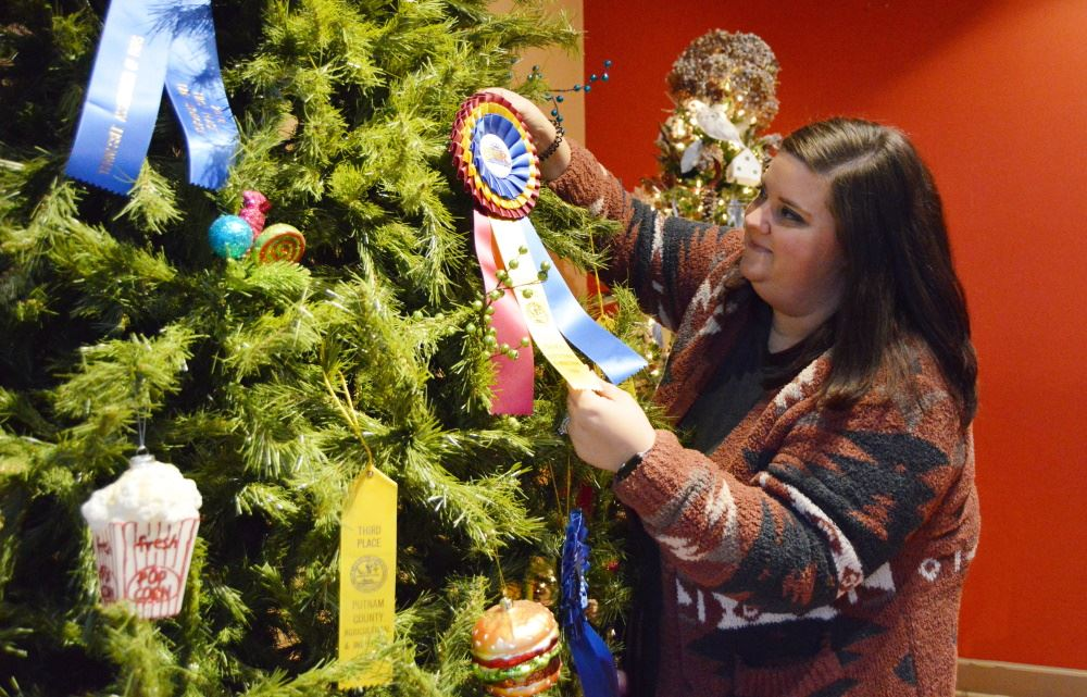 A woman hangs an ornament in the Christmas Forest.