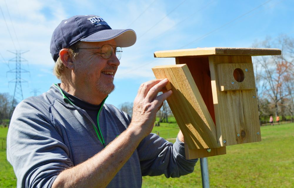 A man looks inside a bluebird box at Cane Creek Park
