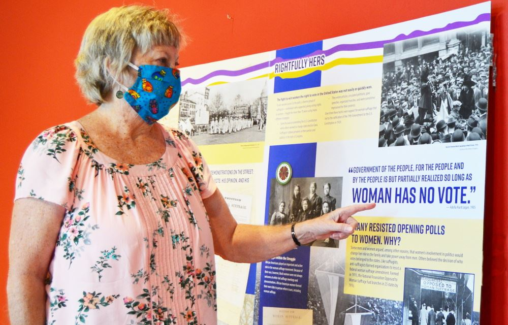 A museum docent looks at the Suffrage Centennial 1920-2020 exhibit at Cookeville History Museum.