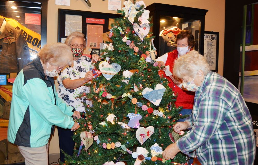 Button Society members decorate their tree in the Christmas Forest at the Cookeville History Museum.